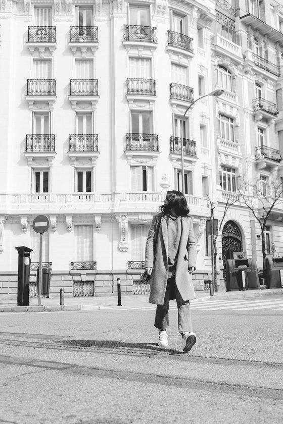 man in black coat walking on sidewalk in grayscale photography